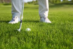 Golf club and ball in grass. Golf ball and golf club in front of golf player Stock Photos