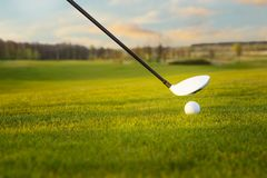 Golf club and ball in grass. Golf ball on tee in front of driver Stock Photo