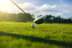 Golf club and ball in grass. Golf ball on tee in front of driver Royalty Free Stock Photos