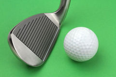 Golf club and ball. On green background, macro shot Royalty Free Stock Photo