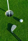 Golf club and ball on the green course. Close up. Top view. Sport, relax, recreation and leisure concept Stock Photos