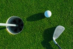 Golf club and ball on the green course. Close up. Top view. Sport, relax, recreation and leisure concept.  royalty free stock image