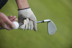 Golf club and ball in hand Stock Image