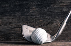 Golf club and ball on old wood Royalty Free Stock Photo