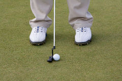 Golf club and ball on tee grass. Closeup of legs with golf club and ball on tee grass, golfer prepares to putt Stock Image
