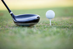 Golf club and ball on tee off. Closeup of a golf club and a golf ball ready for tee off royalty free stock photo