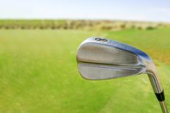 Golf club on course. Close up of 8 iron golf club on sunny green golf course royalty free stock photography