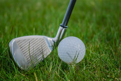 Golf club and golf ball. Closeup on golf club and ball in grass Stock Photos