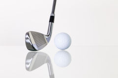 Golf club and golf ball on the glass desk Royalty Free Stock Image