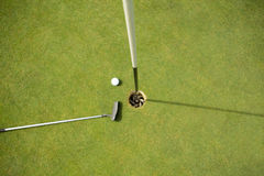 Golf club and golf ball on the putting green beside flag. On a sunny day royalty free stock photography