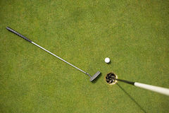 Golf club and golf ball on the putting green beside flag. On a sunny day stock images