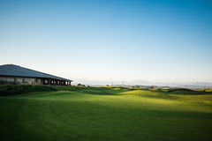 Golf club house with rays of sun at sunset. Beautiful golf club house with rays of sun at sunset Royalty Free Stock Images