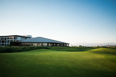 Golf club house with rays of sun at sunset. Beautiful golf club house with rays of sun and mountains at sunset Royalty Free Stock Image