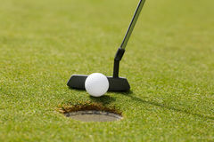 Golf club putting ball at the hole Royalty Free Stock Images