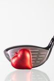 Golf club and red heart on a glass table Royalty Free Stock Photo