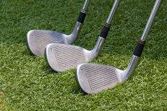 Golf clubs. 3 clubs and emit in the green grass Stock Image