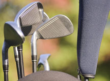 Golf clubs. In a golf bag with autumn foliage as background Royalty Free Stock Photography