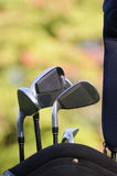 Golf clubs. In a golf bag with autumn foliage as background Royalty Free Stock Photos