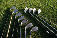 Golf clubs arranged on the green grassy field Stock Photos