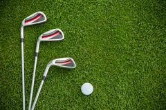 Golf clubs and ball in grass Royalty Free Stock Images