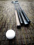 Golf Clubs and Ball in Office on Carpet Royalty Free Stock Photo