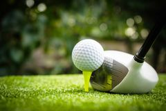 Golf clubs and golf balls on a green lawn in a beautiful golf course royalty free stock photography