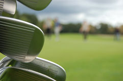 Golf clubs detail with golfers in the distance Royalty Free Stock Photography