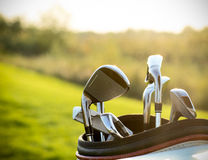 Golf clubs drivers over green field background royalty free stock photo