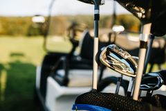 Golf clubs drivers over green field background. Summer sunset royalty free stock photos