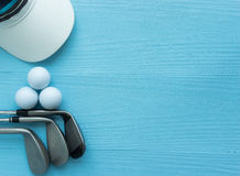 Golf clubs, golf balls, cap. On blue wooden table, with copy space Royalty Free Stock Image