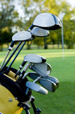 Golf Clubs and Golf Course. A set of golf clubs on a golf course on a beautiful sunny day royalty free stock images