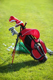 Golf clubs in golfbag, green grass background Stock Photos