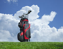 Golf clubs on grass with blue sky and clouds Stock Photos