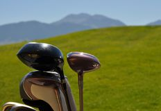 Golf Clubs on Hilly Golf Course. Golf clubs on a hilly golf course with mountain range background Royalty Free Stock Image