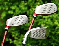 Golf clubs. Image of a red golf clubs on the green this image was taken in bright sun light Royalty Free Stock Image