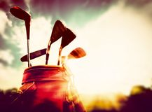 Golf clubs in a leather baggage in vintage, retro style at sunset