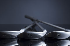 Golf clubs lying on dark blue reflective surface. Golf clubs lying on reflective surface,  on dark blue background with empty copy space for text Stock Images