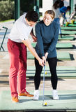 Golf Coach tells a girl how to hit the ball Royalty Free Stock Image