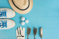 Golf concept : flat lay. Golf concept : panama hat, glove, golf balls, golf clubs, golf shoes on wooden table. Flat lay with copy space Royalty Free Stock Image