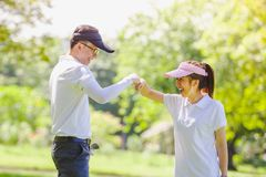 Golf Couple. Asian couple playing golf. Man teaching woman to warm up while standing on field Stock Photos