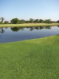 Golf Course. New Golf course with a lake view that has a pebble sea wall stock image