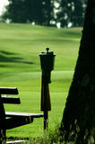 Golf Course. Golf ball cleaner shot in shadow with course in background with narrow DOF Stock Photo