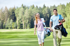 On the golf course. Young couple with clubs on the golf course Stock Photos