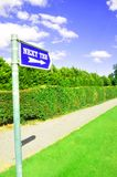 Golf Course sign. A golf course sign saying next tee and blue sky Stock Photo