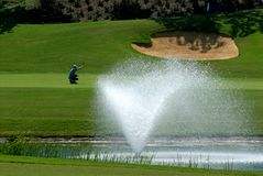 Golf course. Golfer on golf course, fountain in the foreground Royalty Free Stock Photography