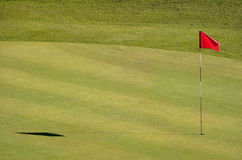 Golf course. With red flag in the hole Stock Photos