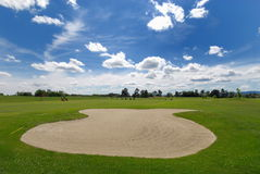 Golf course. Golf ground with bunker and blue sky Royalty Free Stock Photos