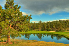 Golf Course. With green and flag behind water hazard Stock Photos