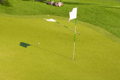 Golf course. Two flags on a green golf course, one lying and one standing. Some golf balls lie on the grass stock photo
