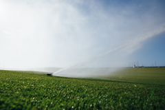 Golf course automatic lawn sprinkler. In action Royalty Free Stock Photos